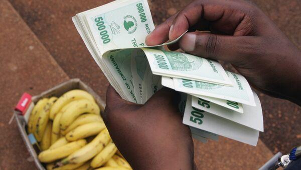 Мужчина считает деньги в Хараре, Зимбабве. 23 января 2008