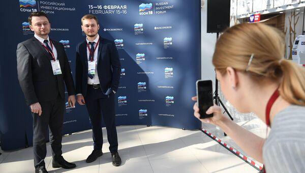 Участники Российского инвестиционного форума в Сочи фотографируются у баннера перед открытием