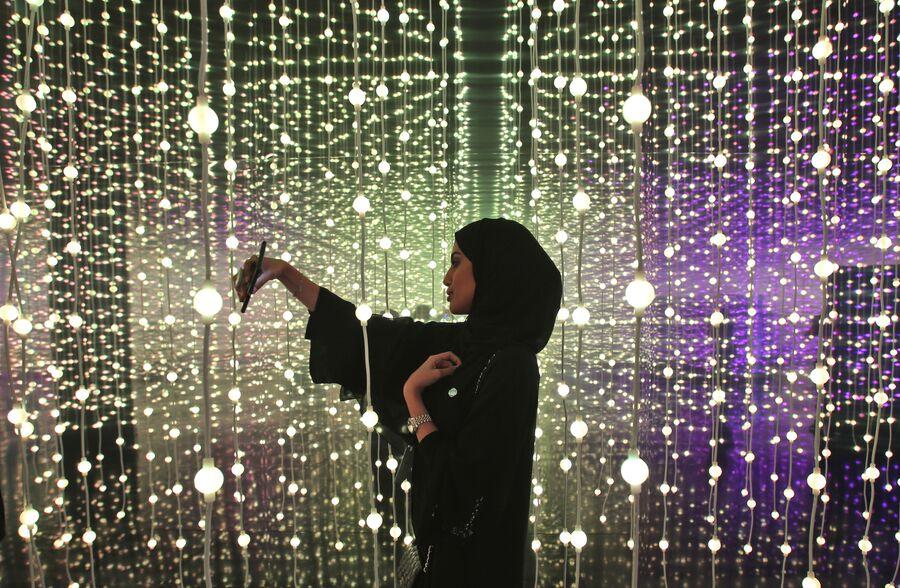 Женщина делает селфи на выставке в Дубае, ОАЭ