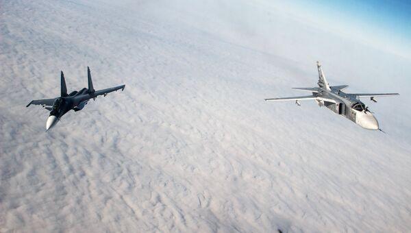 Многоцелевой истребитель Су-30СМ и тактический фронтовой бомбардировщик Су-24М во время лётно-тактических учений
