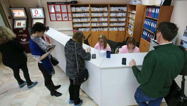 Посетители у регистрационного стола в одной из поликлиник Москвы. Архивное фото