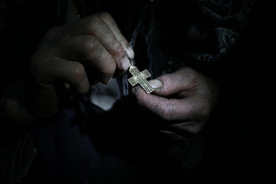 Агафья Лыкова показывает свой нательный крест