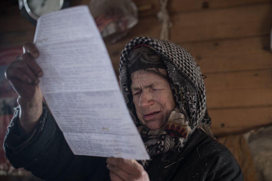 Агафья Лыкова читает письмо, отправленное ей из Боливии