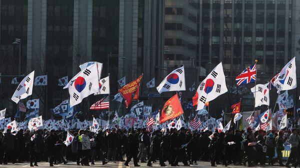 Участники митинга с флагами Южной Кореи, США, Великобритании на одной из улиц в Сеуле