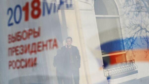 Отражение в окне баннера с информацией о выборах президента России 18 марта 2018. Архивное фото