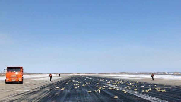 Взлетно-посадочная полоса аэропорта «Якутск» с рассыпанным грузом из самолёта Ан-12. 15 марта 2018