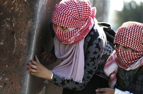 Девушки с масками во время столкновений с израильскими солдатами 12 марта 2018 года в городе Бирзеит на берегу Западного берега