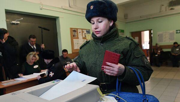 Женщина опускает бюллетень в урну на выборах президента РФ на избирательном участке №76 в Москве. 18 марта 2018