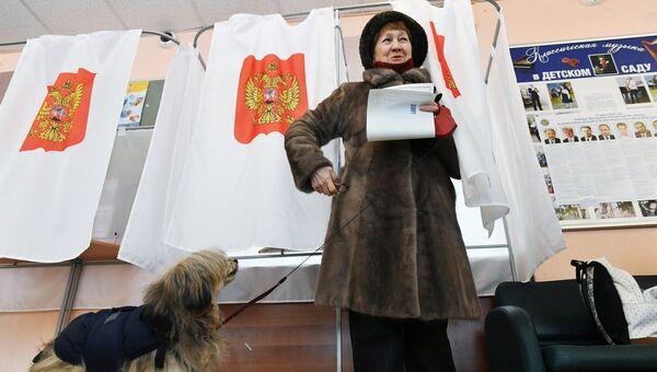 Женщина голосует на выборах президента РФ на избирательном участке в Москве. 18 марта 2018