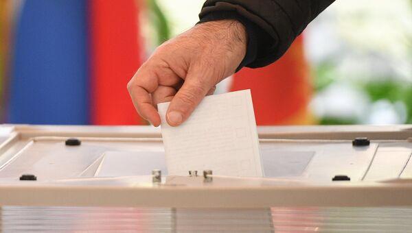 Мужчина голосует на выборах президента Российской Федерации на избирательном участке