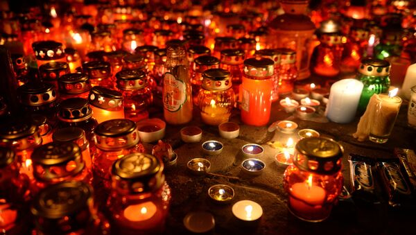 Зажженные свечи возле здания торгового центра Зимняя вишня в Кемерово