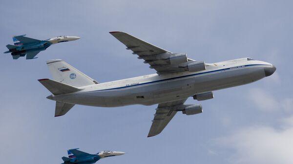 Стратегический военно-транспортный самолет Ан-124 Руслан в сопровождении двух истребителей Су-27