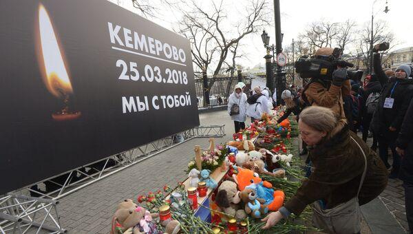 Люди возлагают цветы к мемориалу на Манежной площади в память о погибших в кемеровском торговом центре Зимняя вишня. Архивное фото