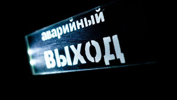 Указатель Аварийный выход в кинотеатре торгового центра. Архивное фото