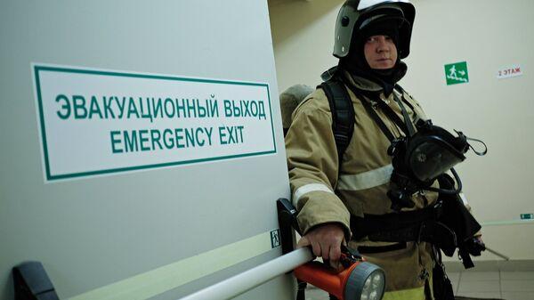 Сотрудник противопожарной службы у эвакуационного выхода в торговом центре. Архивное фото