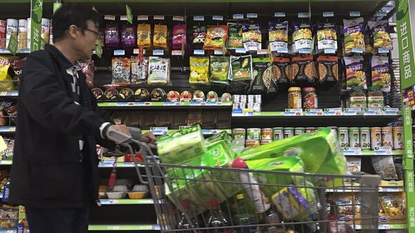 Мужчина у витрины с орехами из США в супермаркете в Пекине. Архивное фото
