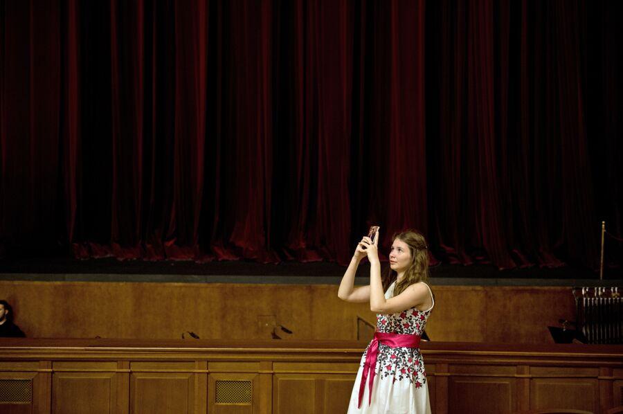 Зрительница делает фотографию в зрительном зале Новосибирского оперного театра перед началом спектакля