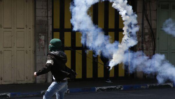 Палестинский демонстрант отбрасывает канистру со слезоточивым газом в сторону израильских сил во время столкновений в Хевроне. 31 марта 2018