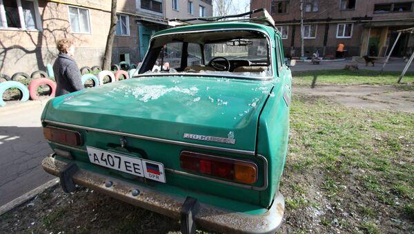 Поврежденный автомобиль во дворе жилого дома после ночного обстрела в Донецке. Архивное фото
