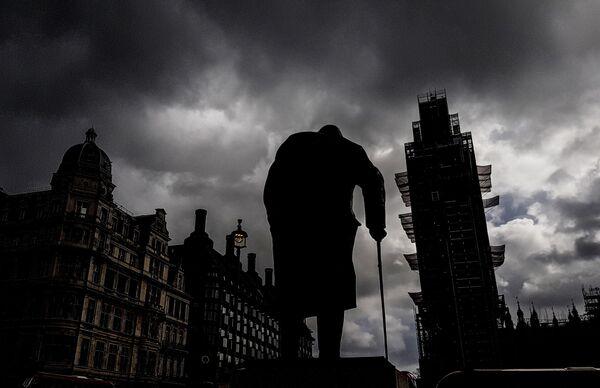 Памятник бывшему премьер-министру Великобритании Уинстону Черчиллю (скульптор Айвор Роберт-Джонс) на Парламентской площади и башня Вестминстерского дворца (Биг-Бен) во время ремонта