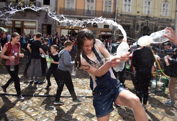 Участники во время праздничных обливаний водой на площади Рынок во Львове