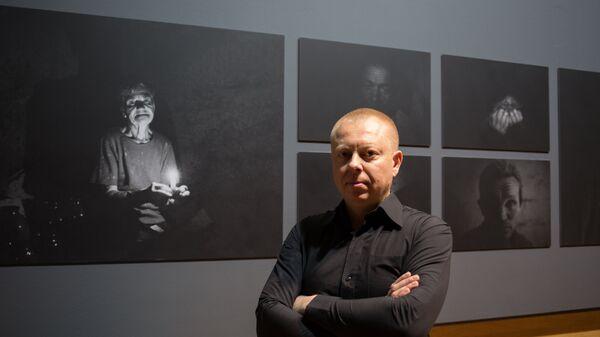 Специальный фотокорреспондент МИА Россия сегодня Валерий Мельников на фоне фотографий из серии Под землей (Underground)