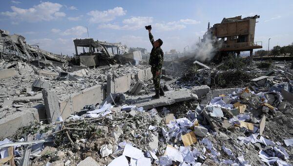Сирийский солдат на месте разрушенного научно-исследовательского центра в Барзе, Сирия. 14 апреля 2018