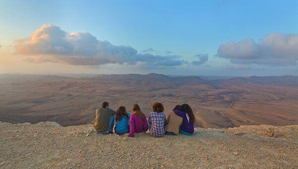 Туристы на краю кратера Рамон в пустыне Негев на рассвете