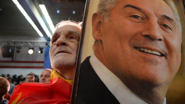 Мужчина с портретом лидера Демократической партии социалистов Черногории Мило Джукановича во время президентских выборов. 15 апреля 2018