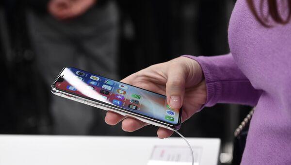 Покупательница рассматривает новый смартфон iPhone X. Архивное фото