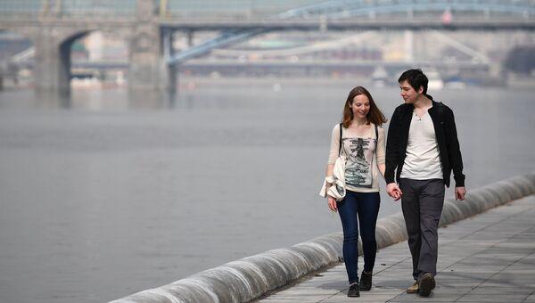 Молодые люди гуляют по набережной
