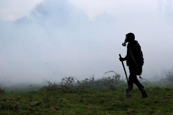Протестующий в облаке слезоточивого газа во время столкновений с французскими жандармами в Нотр-Дам-де-Ланде, Франция