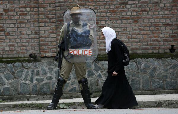 Мусульманская студентка проходит мимо полицейского во время протеста против изнасилования в городе Сринагар, Индия