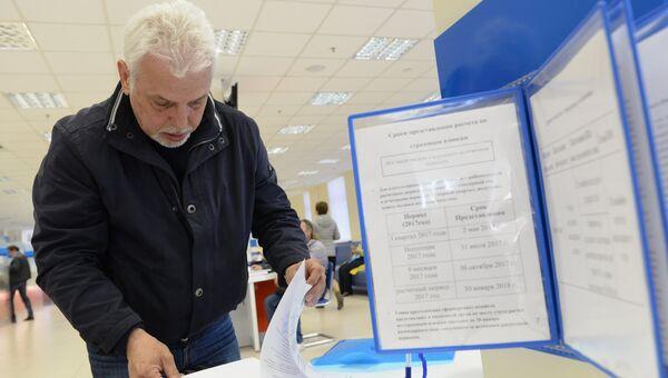 Посетитель заполняет документы в операционном зале инспекции Федеральной налоговой службы РФ в Москве. Архивное фото