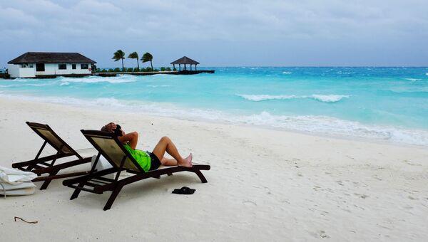Турист на пляже острова Велассару (Мальдивы).