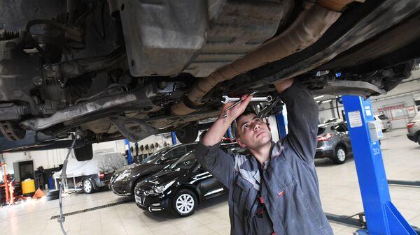 Сотрудник сервисного центра осматривает автомобиль. Архивное фото