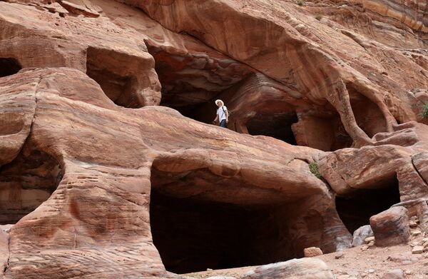 Турист осматривает дома-пещеры кочевников-бедуинов в древнем городе Петра в Иордании