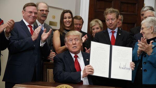 Президент США Дональд Трамп с подписанным указом, который сворачивает Obamacare, США. 12 октября 2017