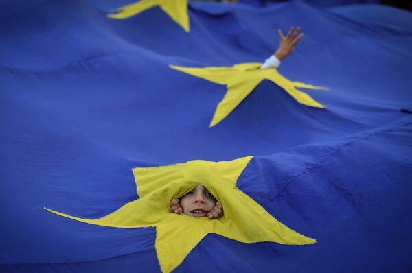 Дети выглядывают из прорезей во флаге ЕС во время акции протеста в Бухаресте, Румыния