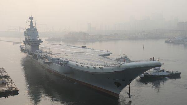 Первый авианосец китайского производства Type 001A поднимает якорь в порту города Далянь в провинции Ляонин в северо-восточном Китае. 13 мая 2018
