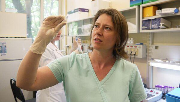 Заведующая лабораторией Ольга Щагина держит в руках пробирку с очищенным ДНК