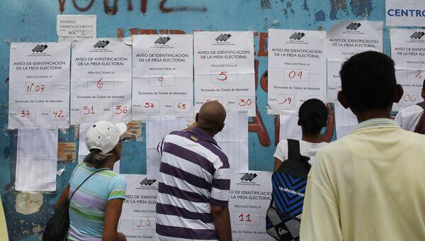 Венесуэльские граждане проверяют списки избирателей на избирательном участке во время президентских выборов в Каракасе, Венесуэла. 20 мая 2018