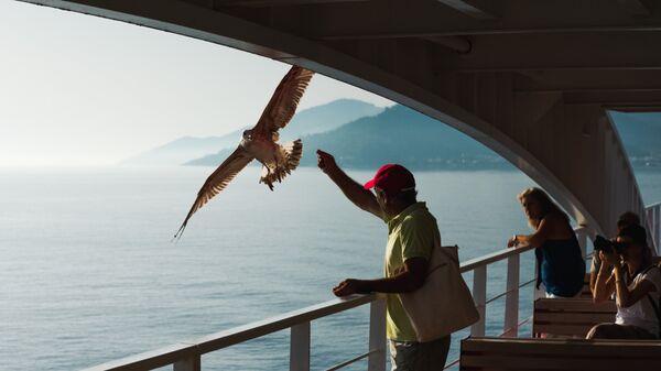 Турист кормит чайку во время круиза на теплоходе по Средиземному морю