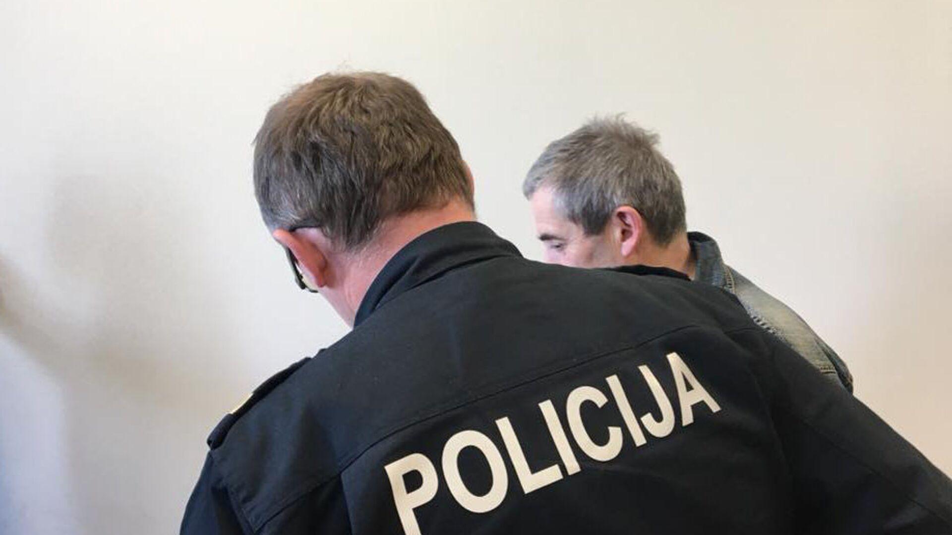 Сотрудник полиции ведет Владимира Линдермана в зал заседаний суда в Риге - РИА Новости, 1920, 13.01.2021