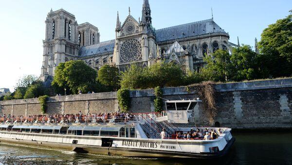 Прогулочный корабль на реке Сене у Собора Парижской Богоматери в Париже