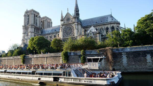 Прогулочный корабль на реке Сене у Собора Парижской Богоматери в Париже. 2018 год
