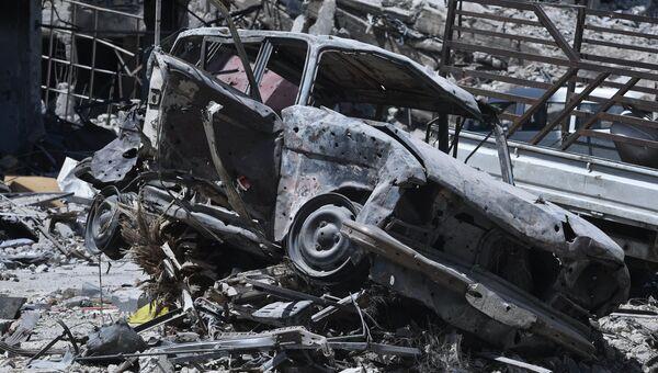 Сожженный автомобиль на территории бывшего лагеря палестинских беженцев Ярмук в Сирии.  Архивное фото