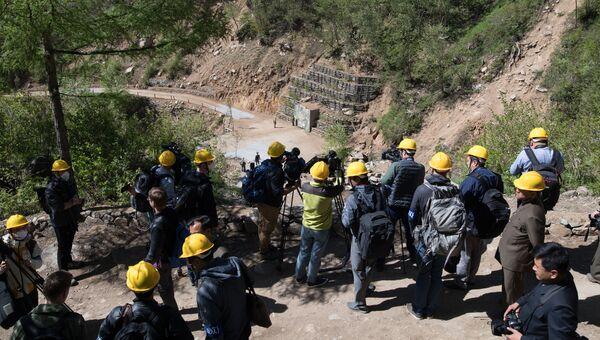 Иностранные журналисты неподалеку от шахты для ядерных испытаний №4 на ядерном полигоне Пхунгери на севере КНДР
