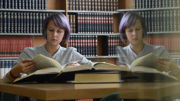 Девушка читает книгу в библиотеке
