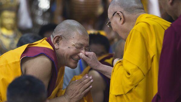 Далай-лама держит монаха на нос во время визита в Дхармсале